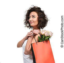 Pretty young brunette woman with shopping bag and pink roses flowers