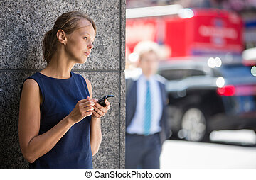Pretty, young businesswoman talking on the phone in front of a modern building in Manhattan