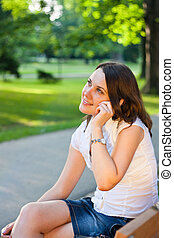 Pretty young businesswoman talking on the phone outdoors in a city park
