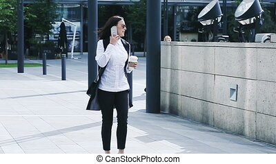 Pretty young businesswoman walking with a cellphone and a coffee cup