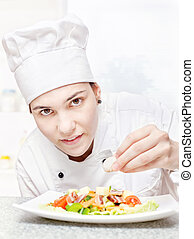 young chef decorating delicious salad