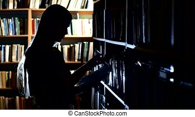 pretty young college student in a library, chooses a book. Close up, back light