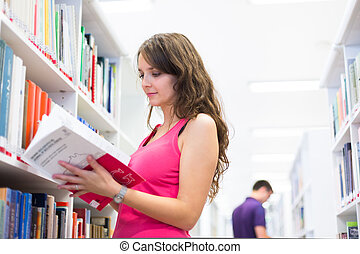 Pretty young college student in a library
