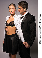 Pretty Young Couple in Fashion Corporate Attire Portrait, Isolated on Gray Background.