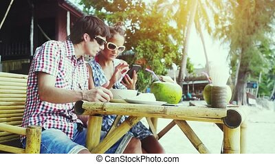 Pretty young couple in sunglasses sitting at a nice cafe by the beach. Girl showing man something in mobile phone. 3840x2160