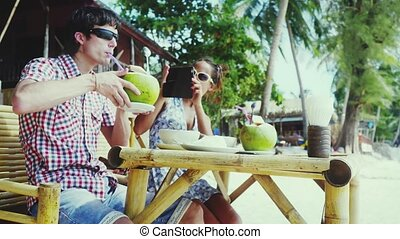 Pretty young couple in sunglasses sitting at a nice cafe by the beach. Girl takes a picture her boyfriend with mobile phone while man drink coconut juice. 3840x2160, 4k
