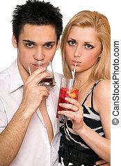 Pretty young couple with cocktails. Isolated