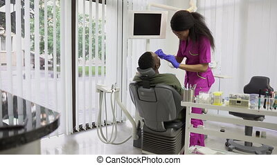 Pretty young female african dentist examining her handsome ...