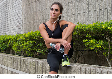 Pretty young female athlete recovering after exercising or running, sitting, listening to music in earphones and looking into the distance