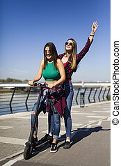 Pretty young female friends riding an electric scooter in the street