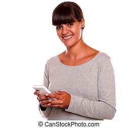 Pretty young female looking at you using cellphone