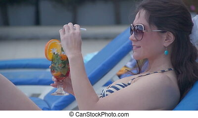 Pretty young female relaxing with fresh cocktail on sunny beach
