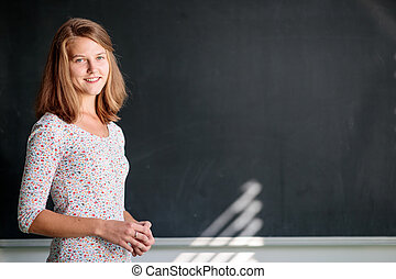 Pretty, young female student in front of a blackboard