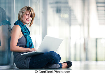 Pretty young female student with a laptop computer