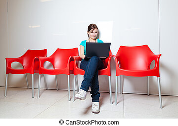 Pretty young female student with laptop