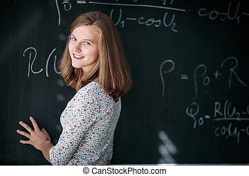 Pretty, young female student/teacher in front of a blackboard during math class