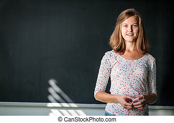 Pretty, young female student/young teacxher in front of a blackboard
