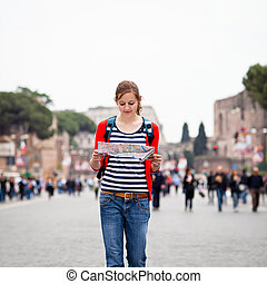 Pretty young female tourist holding a map while walking...