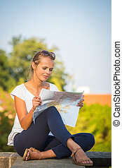 Pretty young female tourist studying a map at the Trajan's forum in Rome, Italy