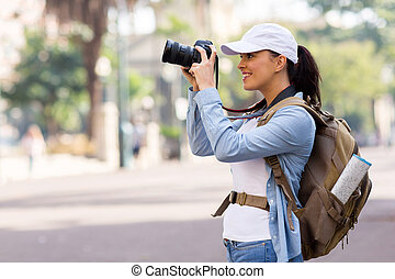 pretty young female tourist taking pictures in the city