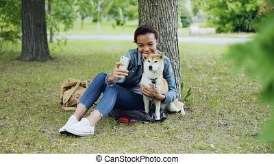 Pretty young girl blogger is taking selfie with purebred dog...