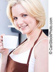 coffee break - pretty young girl in apron having a coffee ...