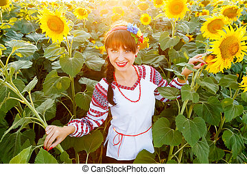 Pretty young girl in embrodery on a sunflower field.