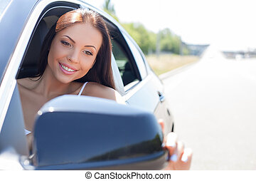Pretty young girl is driving her vehicle