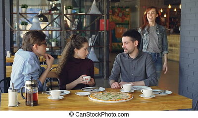 Pretty young girl is meeting her friends in pizza house...