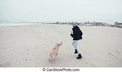 Pretty young girl is playing with a dog on the beach. Happy family on vacation.