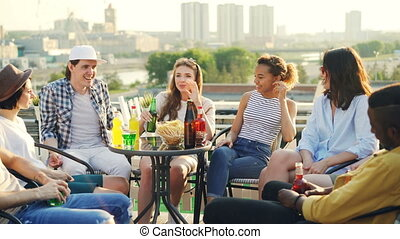 Pretty young girl is telling story to her friends multiethnic group sitting at table on rooftop with food and drinks, beautiful view of city is in background.