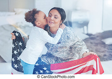Pretty young girl kissing her mother