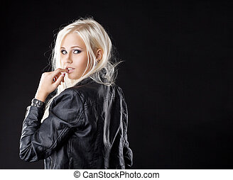 Pretty young blond girl look at camera with desire in leather