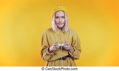 Pretty young girl playing video exciting game on Tv with joystick on yellow studio wall. Using modern technology