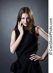 Pretty young girl posing in trendy black dress