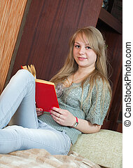 girl reading book on sofa