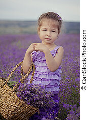 Pretty young girl sitting in lavender field in nice hat boater with purple flower on it.