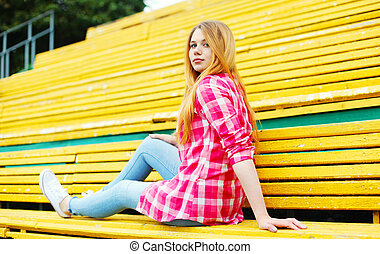 Pretty young girl sitting resting on bench in city park