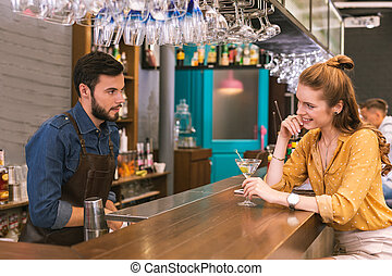 Pretty young girl smiling and flirting with the barman