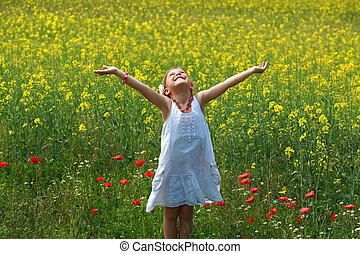 Pretty young girl happy to be surrounded by rapeseed flowers