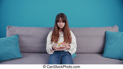 Pretty young girl twisting multicolor Rubik's Cube at home...