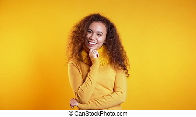 Pretty young girl with curly hair standing on yellow studio background, smiling and flirting. Cute portrait of mixed race woman
