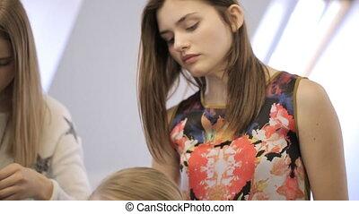 Pretty young girls prepare for photo session in beauty studio.