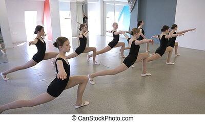 Pretty young girls train in dancing class to develop flexibility.
