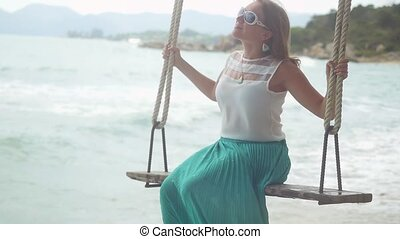 Pretty young happy woman wearing sunglasses relaxes on the swing at the stones beach in slow motion. 1920x1080