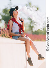 Pretty young hipster asian woman in black hat vape ecig, vaping device at the sunset. Toned image.