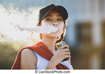 Pretty young asian girl vape popular ecig gadget, vaping device. Happy brunette vaper girl with e-cig. Portrait of smoker female model with electronic cigarette vaporizer. Ejuice vaping with fruit flavor liquid