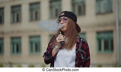 Pretty young hipster woman in black cap vape ecig. Girl vape...