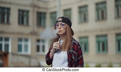 Pretty young girl vape popular ecig gadget,vaping device.Happy brunette vaper girl with e-cig.Portrait of smoker female model with electronic cigarette vaporizer.