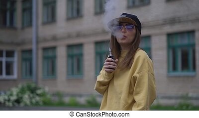 Pretty young hipster woman in black cap yellow hoodie vape ...